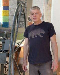 Printmaker Ron Rumford standing next to printing press