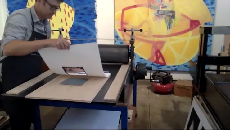 Phil Sanders in his studio pulling a print through the press