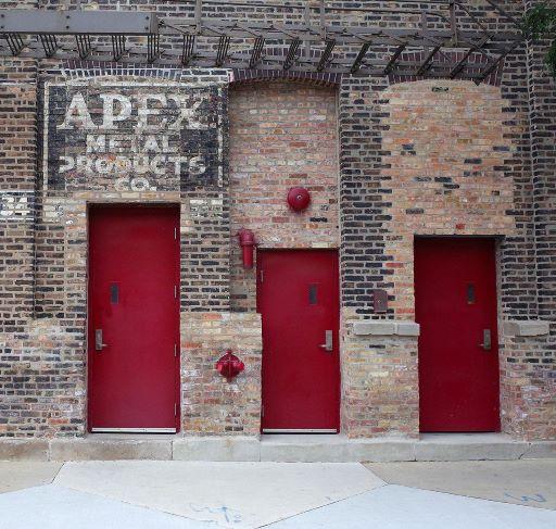 Exterior brick facade, 3 red doors Apex Metal